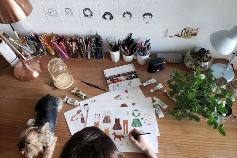 Woman sitting at desk designing watercolor